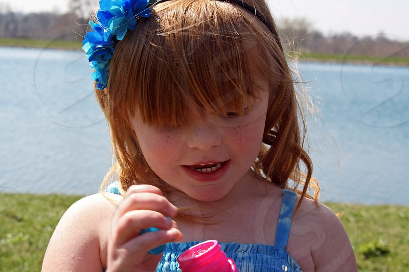 child; girl; happy; bubbles; water; spring; red hair; flowers; curls; freckles; innocent photo