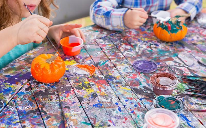 Caucasian children painting a miniature pumpkin at a local autumn festival photo