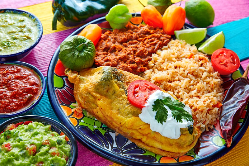 Chili relleno chili pepper poblano filled with cheese in dish with with rice and frijoles beans photo