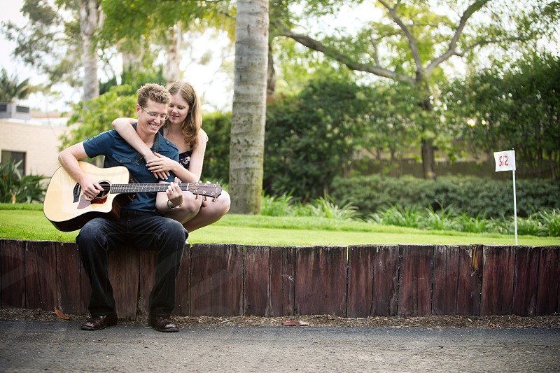 A young couple playing guitar.  Sit golf wall wood flag 512 music happy love trust trees grass course hug rest relax content photo
