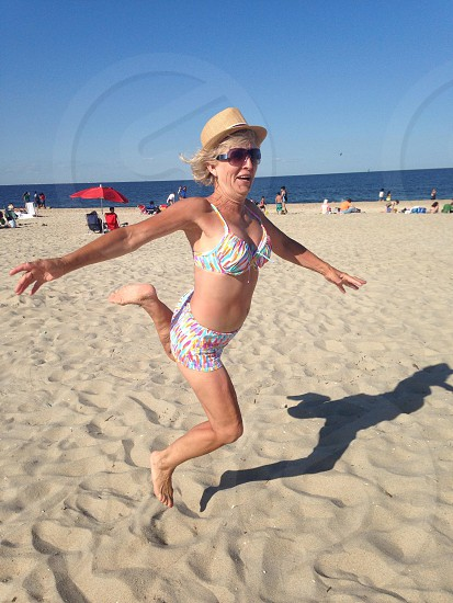 grandmother active adult jumping beach sand  photo