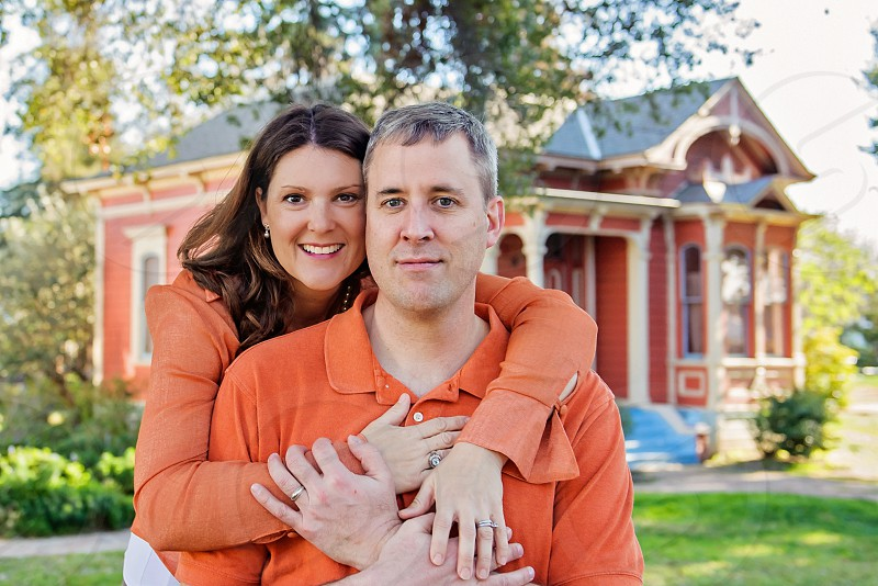 Smiling Caucasian Couple standing in front of cute Victorian House photo