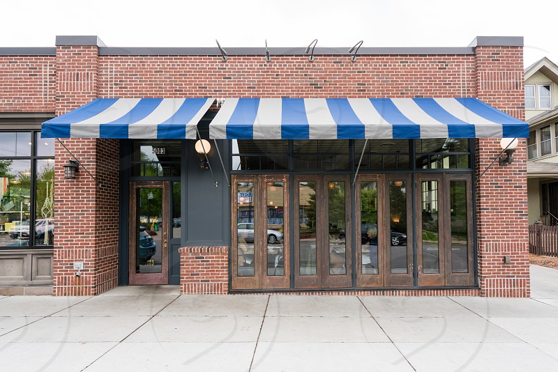 brown concrete brick shop with brown wooden framed glass window and door and white and blue awnings during daytime photo