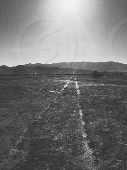 A triangle forms when the lines of car tracks converge in the desert photo