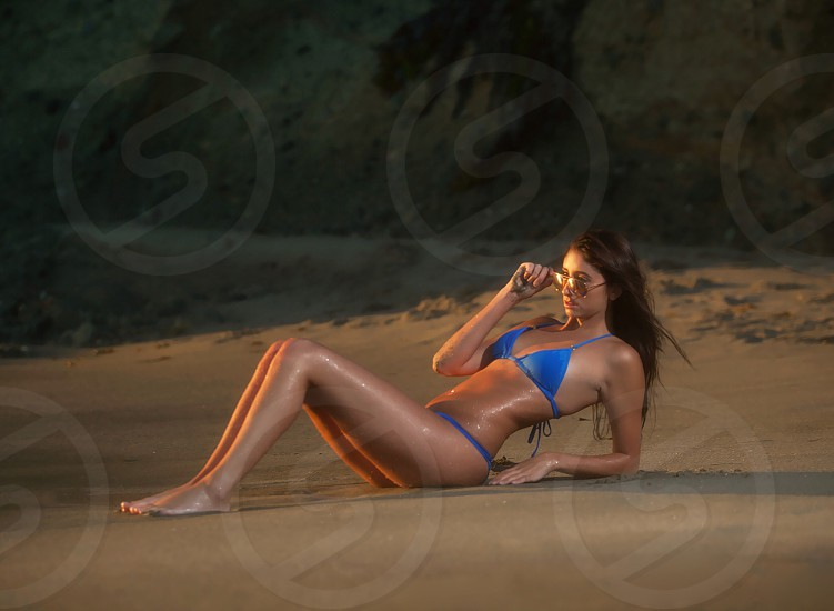 woman in blue brassiere and panty lying on sand photo