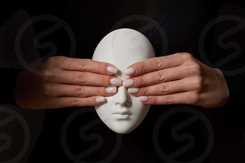 Girl's hands close eyes of plaster mask face on a black background. See no evil. Concept three wise monkeys. Place for text. photo