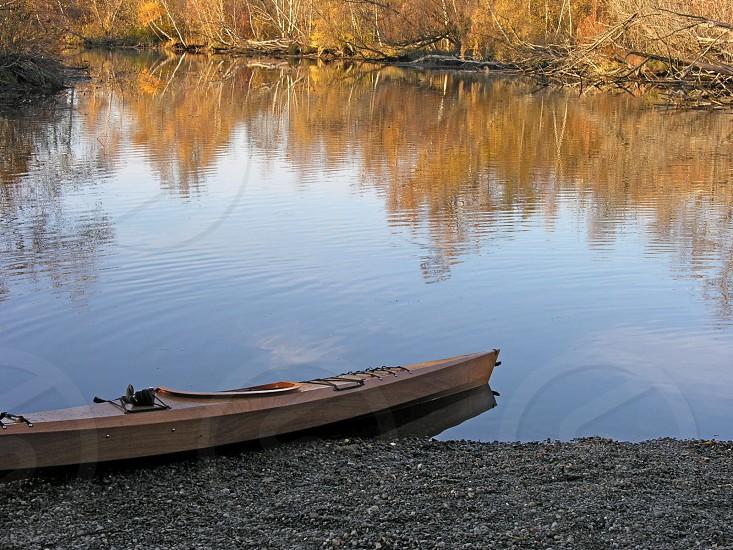 canoe water pond fall leaves reflection vacant solitary alone empty ripples gravel shore shoreline fall anticipation nature serene photo