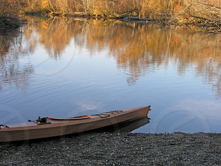 canoe bank rocks shore shoreline lake inlet fall colors reflection foliage ripples water still calm recreation entertainment photo