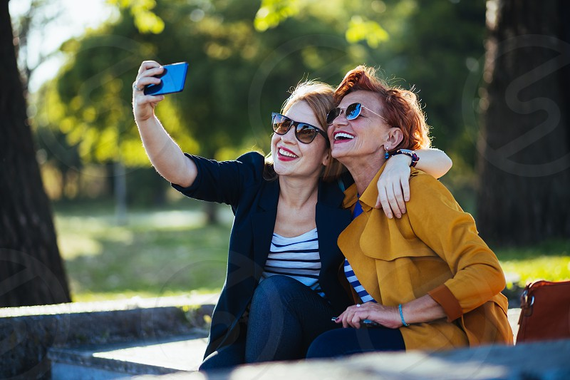 Mature mother and adult daughter taking selfie in the park photo