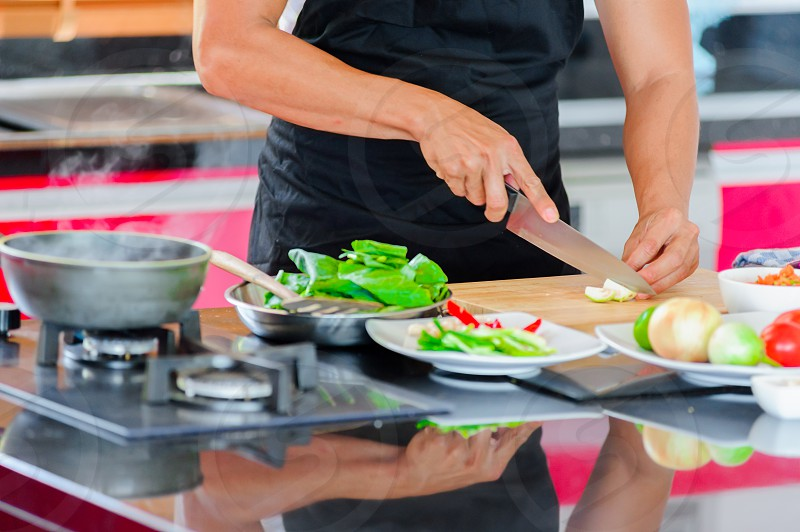 Private Thai chef cooking in a modern style home kitchen. Making Thai food: mixed vegetables oyster sauce photo