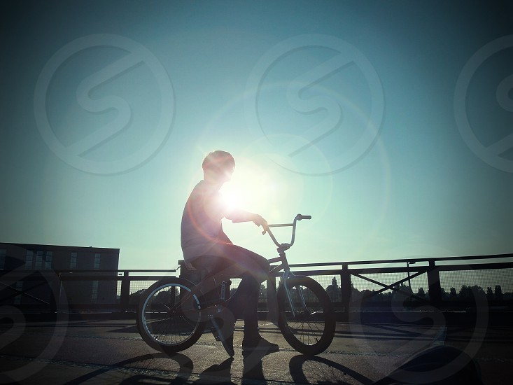 sunset with a silhouette of someone on a bike with a lens flare  photo
