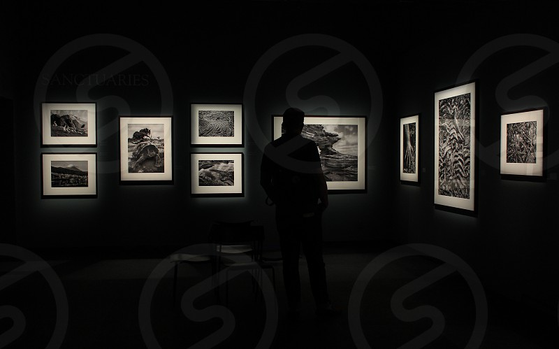 Silhouette of a person looking at art frames on a wall in a gallery. photo