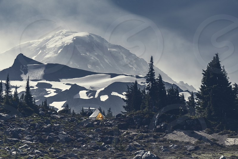 Moonlit tent site under magnificent snow and glacier covered mountain. photo