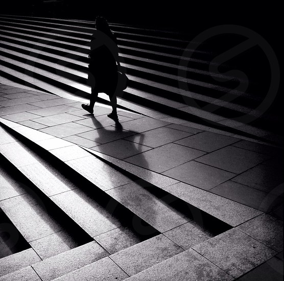 A woman walks between steps near Saint Paul's Cathedral in London England. As she walks the low afternoon sun casts long shadows.  photo