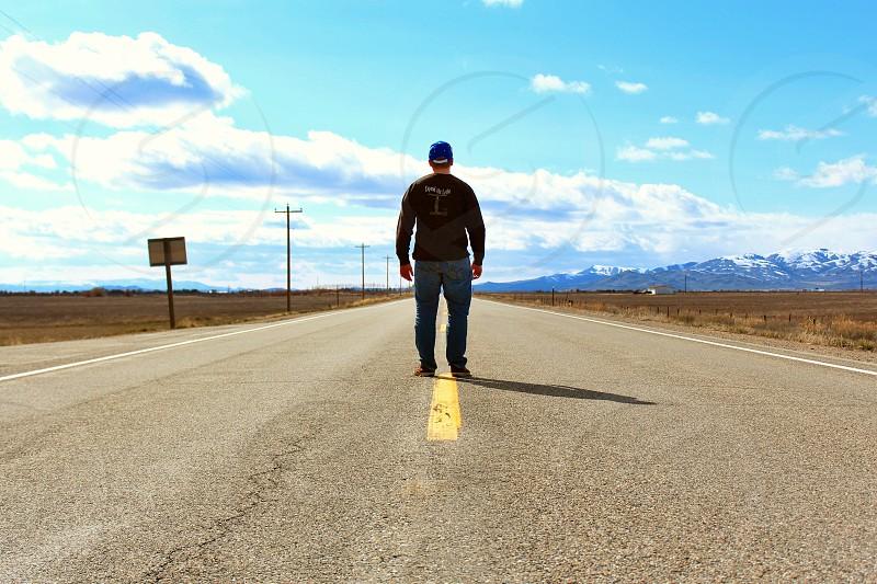 man walking on road photo