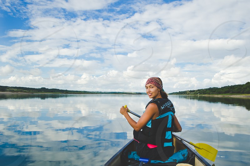 Woman paddling a canoe on a clear river clouds reflecting off the surface.  photo
