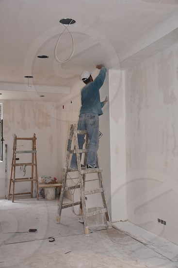 man in blue sweater touching white ceiling while on step ladder inside the room photo