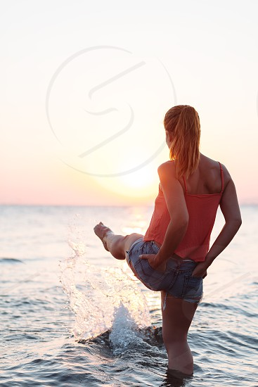 Young woman enjoying sea and sunset photo