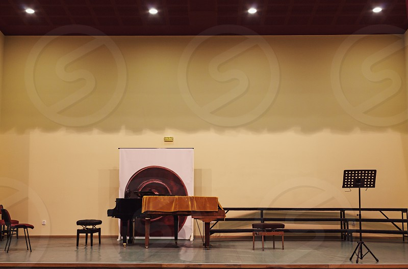 Details of an empty small concert hall with stage piano and some chairs on it. photo