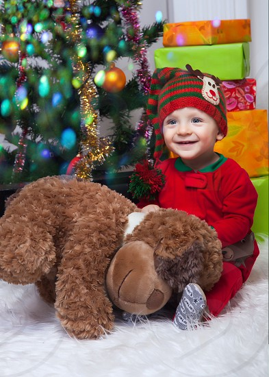 boy wearing red and green knitted cap holding brown animal plush toy photo