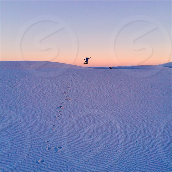footprints on sand and person jumping with sunrise view photo