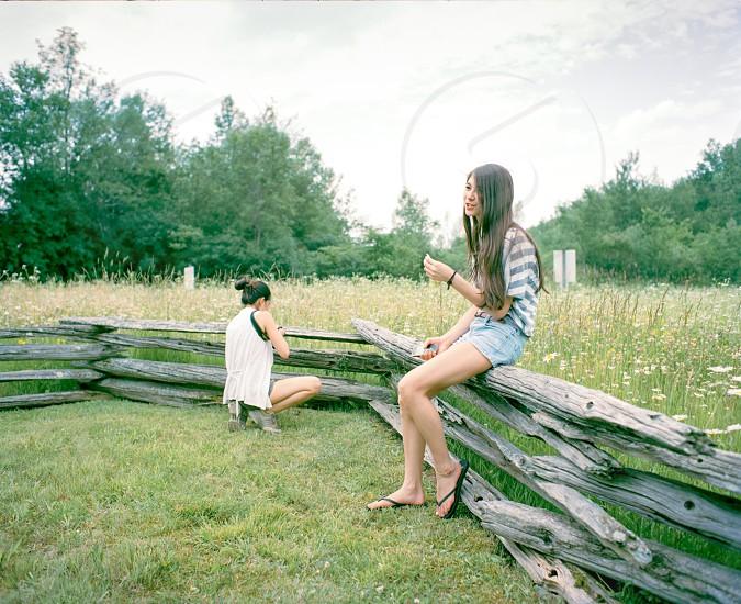 2 women near gray wooden fence photo