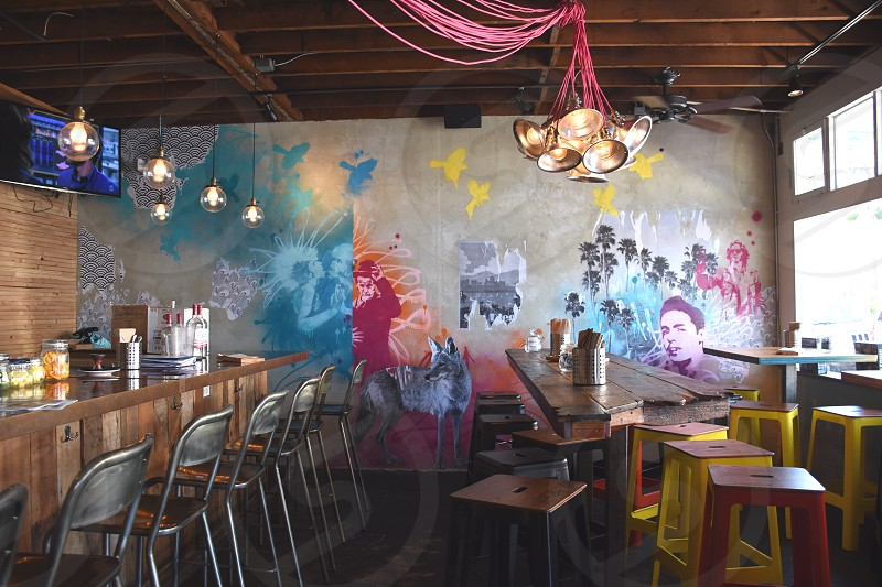 grey bar chairs and bar stool near painted wall in bar photo