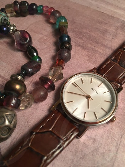 brown leather strap round bulova analog watch beside brown teal and black beaded charm bracelet photo
