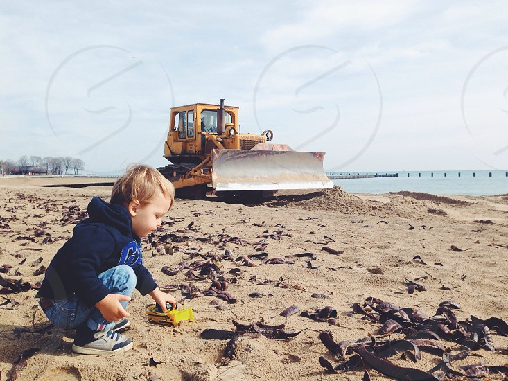 boy playing on beach sand near bulldozer photography photo