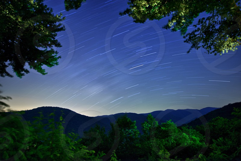 Star Trails in the mountains featuring green trees. photo
