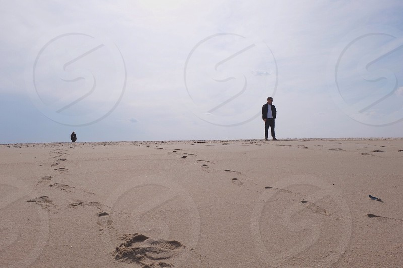 man on a beach with footprints photo