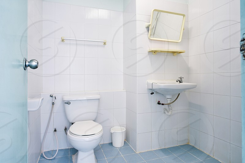 Standard facilities of generic toilet room of small hotel or apartment with flush toilet sink towel rack and washbasin for flip glass mirror photo