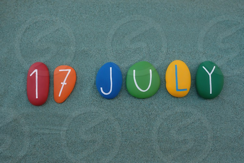 17 July calendar date composed with multi colored stones over green sand photo