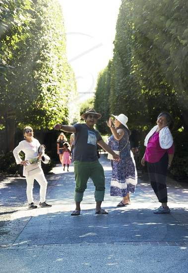 Summer fun in the sun friends family people laughing dancing fooling around in the sun tunnel of trees photo
