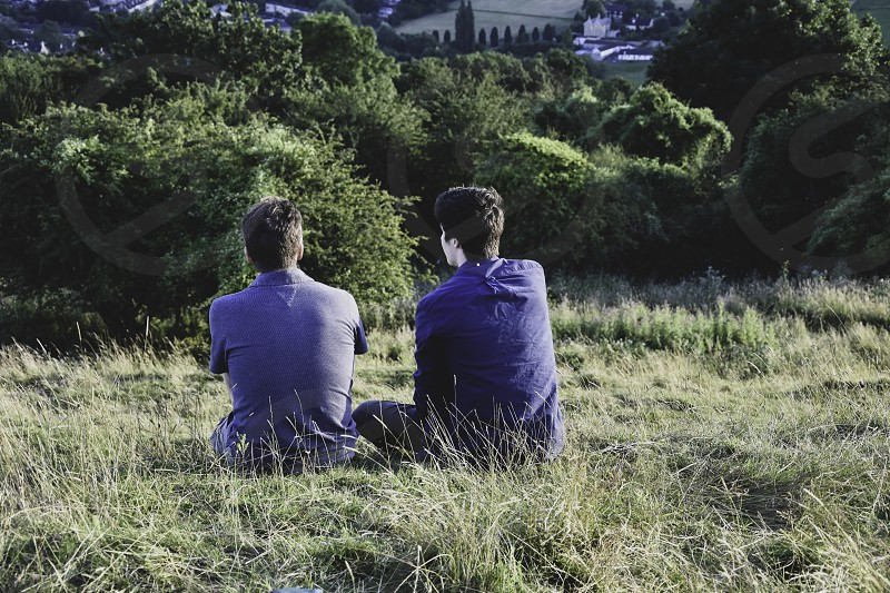 Two men sitting chatting on hillside. photo
