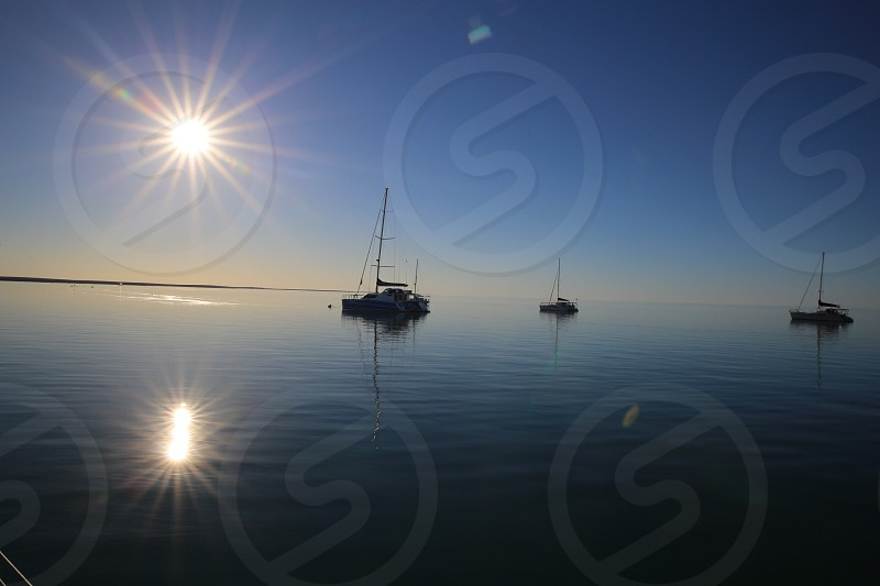 sunrise over the sea and sailboats photo
