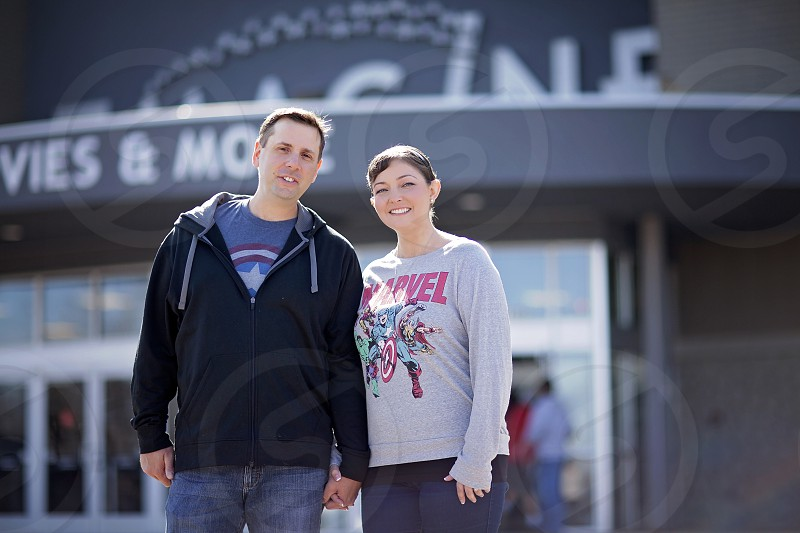 Couple holding hands in front of a movie theatre photo