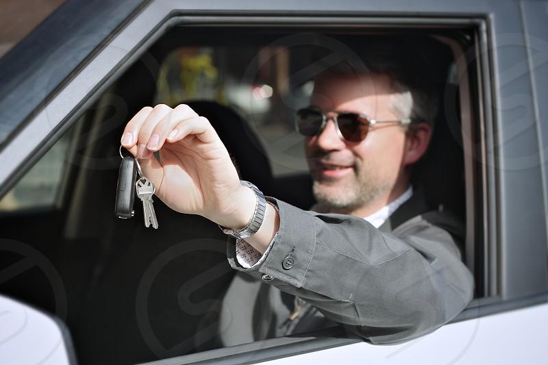 man in car holding keys photo