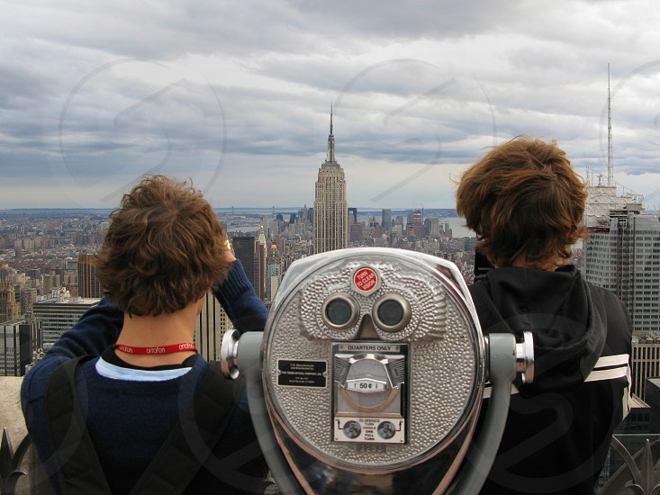 man in black hoodie and man in blue long sleeve shirt in front of silver coin operated binoculars on viewing deck near empire state building in new york under white sunny cloudy sky photo