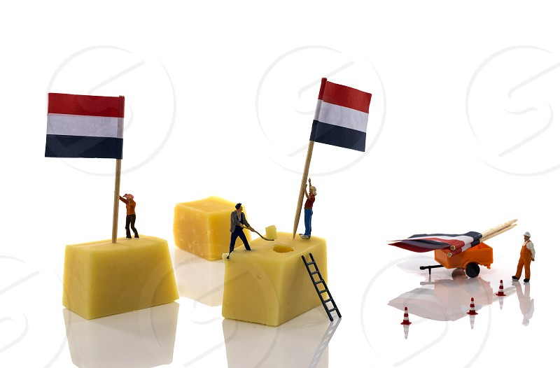 little people putting the dutch red white and blue flags on dutch cheese photo