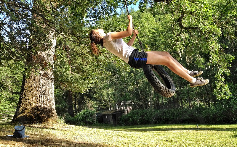 woman in white shirt and black shorts riding on black tire swing photo