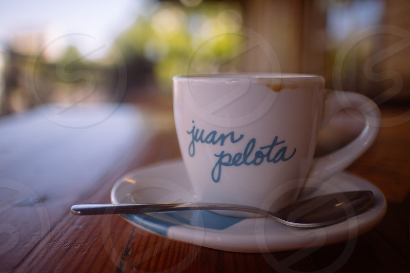 teal juan pelota printed white ceramic mug on white ceramic saucer photo