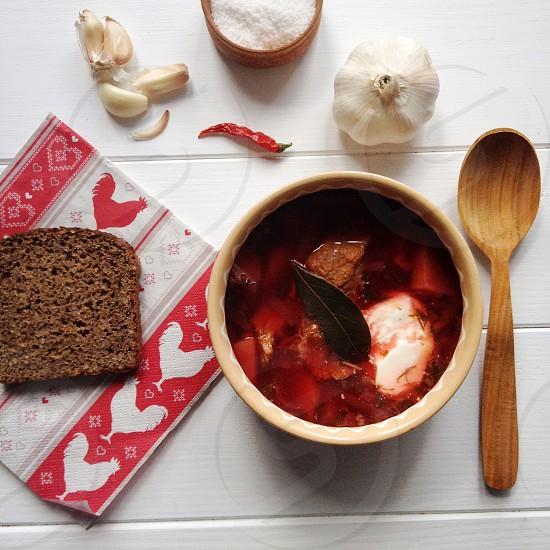 red soup in ceramic ramekin on table photo