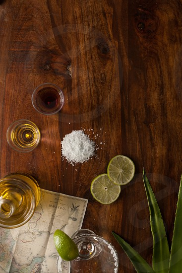 tequila with salt and sliced lemon on brown table photo