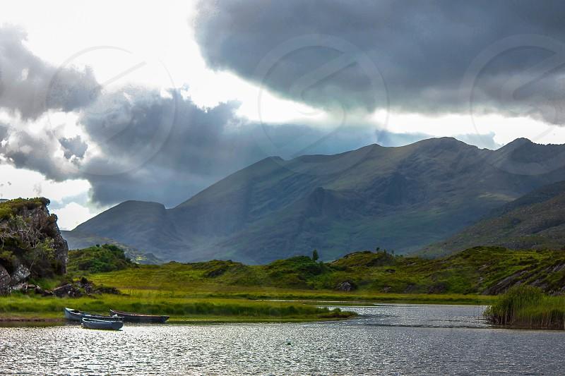 boats on a river near a mountain photo