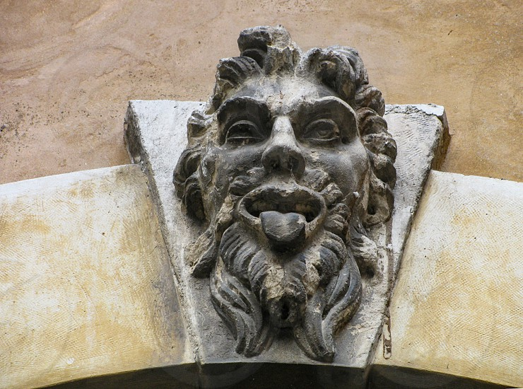 The keystone of an archway of a building in the Palazzo del Capitano in Verona Italy is surmounted by a grotesque face of carved stone called a mascaron or mask. photo