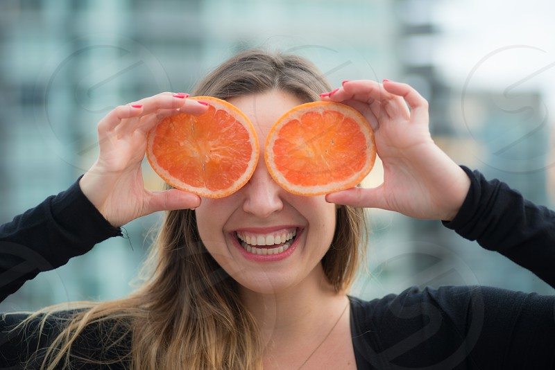 woman covering her eyes with sliced large oranges photo