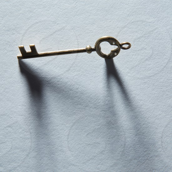 Antique golden door key with shadow isolated on grey background. Blank copy space may be used for any emotions or ideas. photo