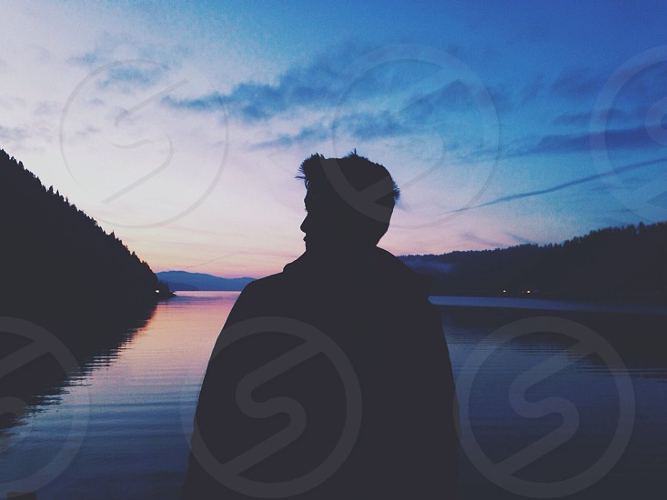 man's silhouette looking at stratus clouds photo