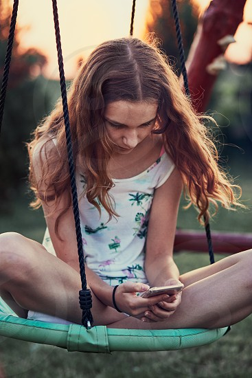 Young woman using mobile phone smartphone sitting on swing in a backyard photo